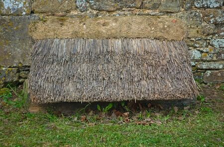Old style cane canopy next to an stone wall Stockfoto
