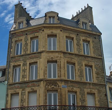Old traditional French stone building with wooden windows