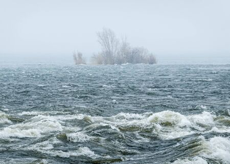 foggy view of an island across the river in a snowstorm in winter 2019 - 2020 Stok Fotoğraf