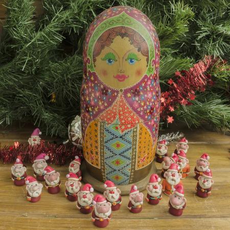 modeling clay: Painted wooden matrioshka doll  and Santa Clauses  from modeling clay. Santa Clauses  around   matrioszka doll.