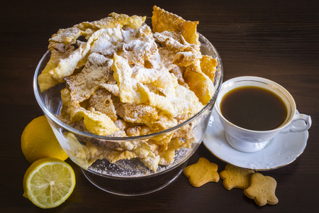 polish lithuanian: Sprinkle with powdered sugar, fried plate of shortcake dough. Dessert Polish and Lithuanian cuisine - faworki (angel wings). Still life. Faworki in a glass vase, coffee in a porcelain cup, lemons and shortbread on a dark background.