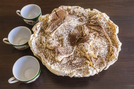 chit: Meringue Cake with chocolate chips and three coffee cups. Still life. Polish cuisine. Stock Photo