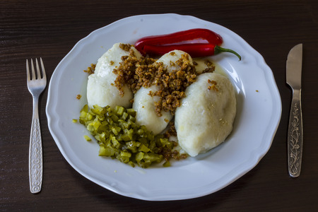 encurtidos: Potato dumplings - a traditional regional dish. Polish and Lithuanian cuisine. With pickles, fried bacon and paprika White plate, knife and fork on a dark background.