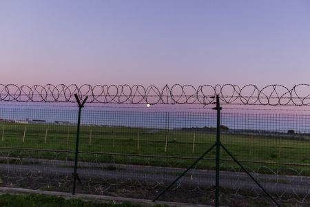The sun sets behind a barbed wire fence. Symbolic picture quiet summer evening.