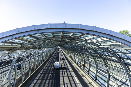 Cars on the road in the sound-absorbing tunnel. Metal structure and glass. Modern technology in the city of Warsaw, Poland.  Stock Photo
