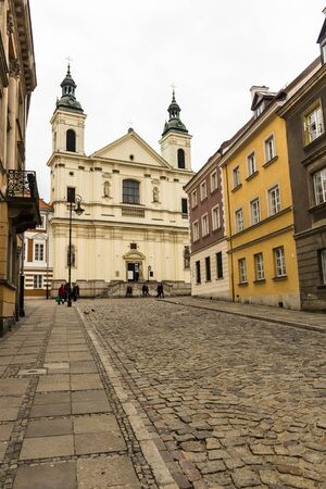 The area of the Old Town in Warsaw, Poland . An old street with nineteenth-century houses, a street lamp and a baroque church. Stock Photo