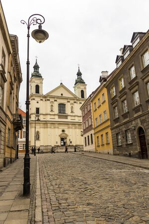 The area of the Old Town in Warsaw, Poland . An old street with nineteenth-century houses, a street lamp and a baroque church. Editorial