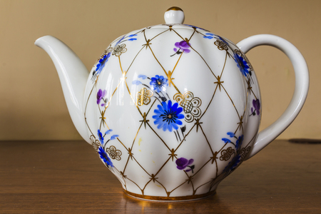 antique factory: Porcelain teapot with golden pattern and blue flowers. Hand-painted old sets. Imperial Porcelain Factory.  Stock Photo