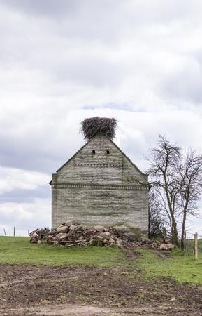 A huge nest of a stork on a brick barn. Spring in the region  Podlasie, Poland.