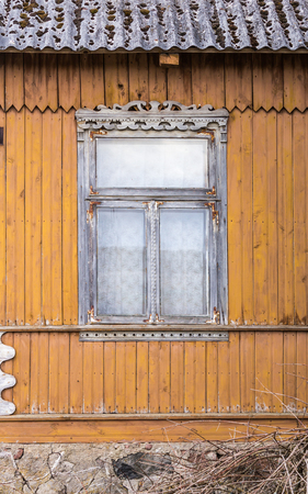 An abandoned wooden house with walls painted yellow-orange paint. Window with carved clypeus. Spring in the Region Podlasie, Poland. Stock Photo