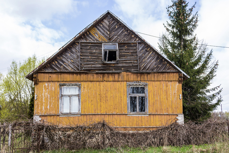 An abandoned wooden house with walls painted yellow-orange paint. Spring in the Region Podlasie, Poland.