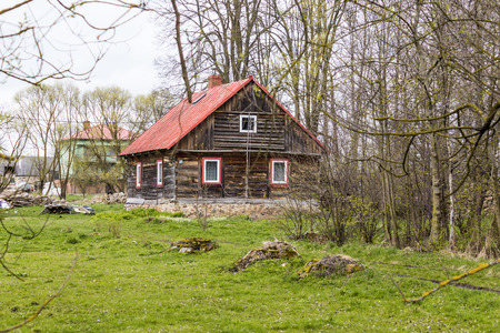 Renovated old wooden house of the beams on the edge of the village near the forest. . Spring in the Region Podlasie, Poland. Foto de archivo