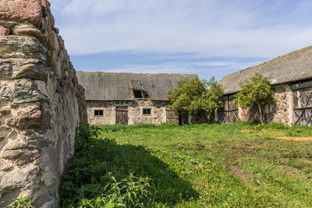The farmyard is an agricultural abandoned farm. The old collapsed barns. The end of the summer . Podlasie, Poland.