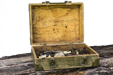 garage: Old plywood toolbox on a old board. Belonged to an electrician or a plumber. Dyed green. With an iron handle and metal locks. Isolated on white background.