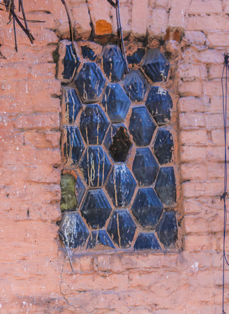 grid pattern: The old window in the old house. Hexagonal grid and hexagonal glass blocks. Stock Photo