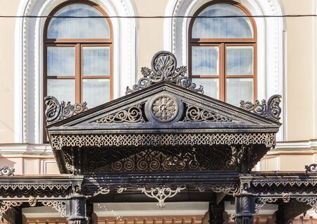 Cast-iron decorative canopy above the entrance. Molded construction on decorative cast-iron columns. The end of the 19th century. Old town district. Moscow, Russia .