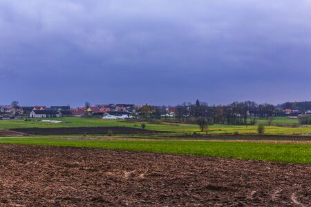 Plowed field after the rain. The village in the background. Late autumn. Cloudy day. Podlasie, Poland. Stock Photo