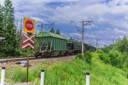 A road sign warning, about the danger at the railway crossing.The locomotive pulls a large freight train. Summer sunny day, green forest. Stock Photo