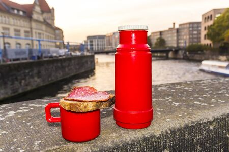 A red thermos and a sandwich with sausage salami. Granite parapet on the embankment of the river Spree. Berlin, Germany. Stock Photo