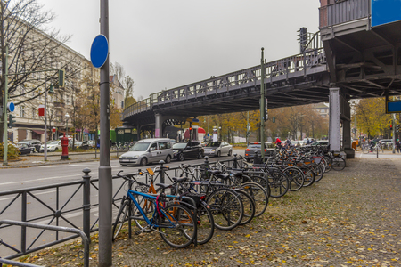 Bicycle parking near the station of the aboveground metro. Metal construction overpass Skytrain pass over the street. Berlin, Germany.