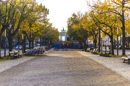 Repair on the Boulevard Under der Linden. Yellow leaves of trees and empty benches. At the end of the Boulevard Brandenburg Gate. Berlin, Germany .