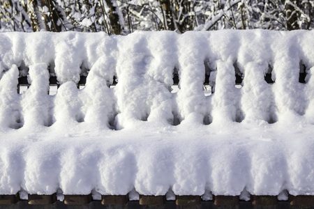 Bench in the park after a heavy snowfall.  Interesting photo for the site about nature, parks and seasons. Stock Photo