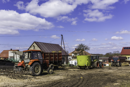 Agricultural machinery and equipment . Tractor with a harrow for cultivating plowed land. The yard of a dairy farm. Podlaskie, Poland. 스톡 콘텐츠