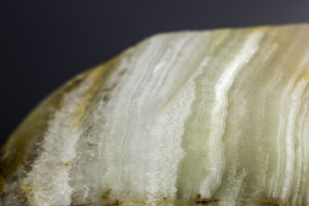 Macro photo texture of polished onyx stone on a gray background. Photo for the site about geology, stones, jewelry, handwork, textures,art, astronomy.