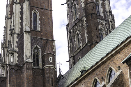 Two towers of the cathedral in the Gothic style. Facades,a copper spire, sculptures,stone decor. Cathedral of St. John the Baptist in Wroclaw, Poland. 免版税图像