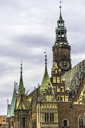 Facades, roofs,sculptures,stone decoration and towers of the medieval Town Hall. Mixed style of architecture - Gothic and Baroque. Vroslav, Poland.