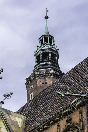 Brick tower with a tower clock. Part of the medieval Town Hall. Mixed style of architecture - Gothic and Baroque. The city of Vroslav, Poland.