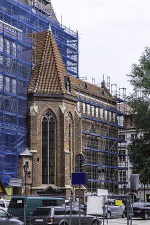 Repair of the church in the Gothic style.Transsept with windows of the southern facade.Scaffolding, blue grid. St. Elizabeth Church in Wroclaw,Poland. 免版税图像