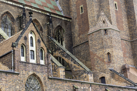 Exterior of a brick cathedral in the Gothic style. Towers, windows, stone decor, flying buttress,roof tiles. St.Mary Magdalene Church. Wroclaw,Poland. 免版税图像