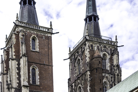 Two towers of the cathedral in the Gothic style. Facades,a copper spire, sculptures,stone decor. Cathedral of St. John the Baptist in Wroclaw, Poland. Archivio Fotografico