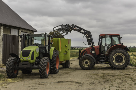 Agricultural machinery and equipment.The tractor with the loader loads a bale of silage in the distributor of mixed fodders for cows.Podlasie, Poland. Stock fotó