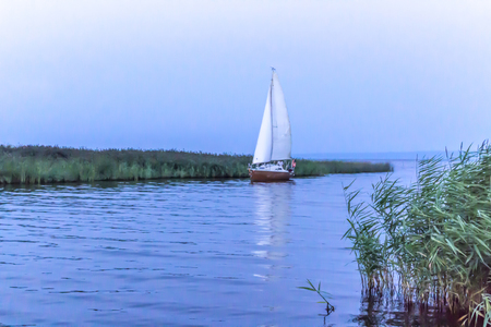 Vistula Bay is a hot summer day. The sailboat sails into the port. Site about travel, fishing, nature, sea, yachts, ships.