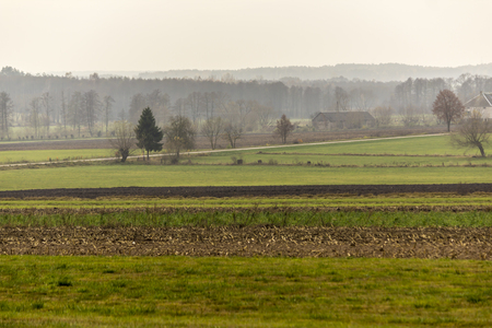 Late autumn.Green meadows and plowed fields in the foreground.Lonely brick house in the background.Site about agroindustry, farming, weather, seasons.
