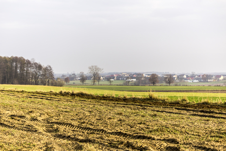 Late autumn. Meadows and plowed fields in the foreground. Village in the background. Site about agroindustry, farming, weather, seasons, art, romance.