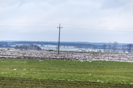 There is a bit of snow on the green meadows and plowed fields.In the middle of the field are pillar and power wires.The beginning of winter in Europe. 스톡 콘텐츠