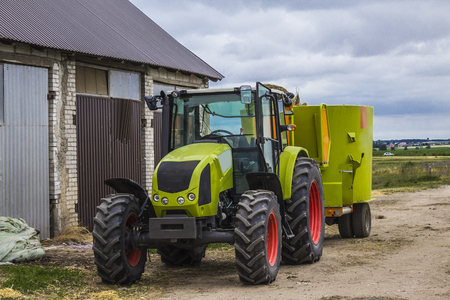 Tractor with a trailer for mixing and distribution of feed for cows. Behind the tractor is a barn and fields. Necessary equipment for a dairy farm. Stockfoto