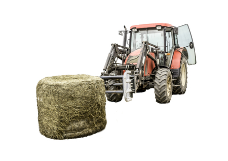 Unpacked from the membrane a silage bale and a tractor with a forklift. Isolated photo. Necessary equipment for a dairy farm.