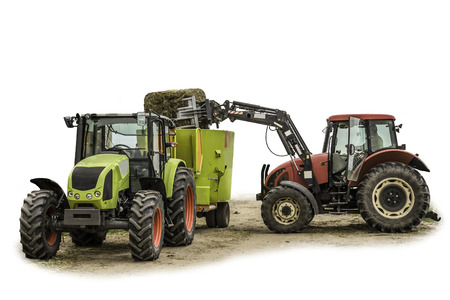 The tractor with the loader loads a bale of silage in the distributor of mixed fodders for cows.Isolated photo. Necessary equipment for a dairy farm. Stock fotó