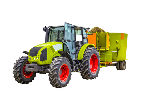 Tractor with a trailer for mixing and distribution of feed for cows. Isolated photo. Necessary equipment for a dairy farm.
