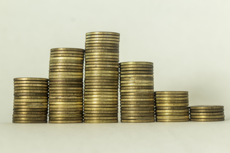 Pile di monete di rame su uno sfondo bianco. Movimento lungo l'onda sinusoidale. Una buona immagine per un sito su finanza, denaro, collezioni, relazioni. Archivio Fotografico