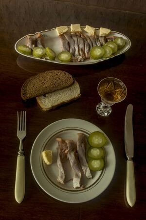 Sliced salmon fillet cut into pieces.Served with pickled cucumbers, butter, vodka and bread. Dark background.A site about cuisine and cookery.