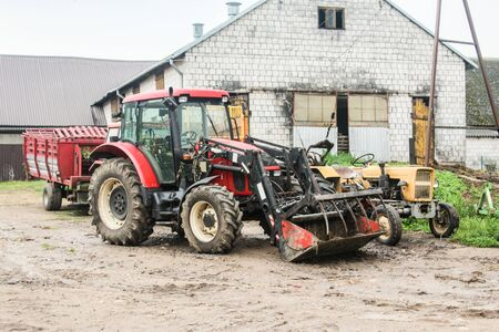 Red tractor with a lift for various works in the yard of a dairy farm. Cowshed in the background. Podlasie, Poland. Stok Fotoğraf