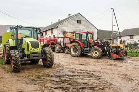 Green and red tractors and agricultural equipment in the yard of a dairy farm. Cowshed in the background. Podlasie, Poland.