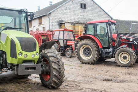 Red and green tractors and agricultural equipment in the yard of a dairy farm. Close up. Cowshed in the background. Podlasie, Poland.