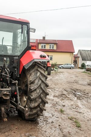 Red tractor  in the courtyard of a dairy farm. View from the back. Apartment building and car in the background. Podlasie, Poland.