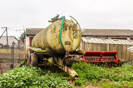Tank for various liquids on a dairy farm. Barn and seeder in the background. Podlasie, Poland.